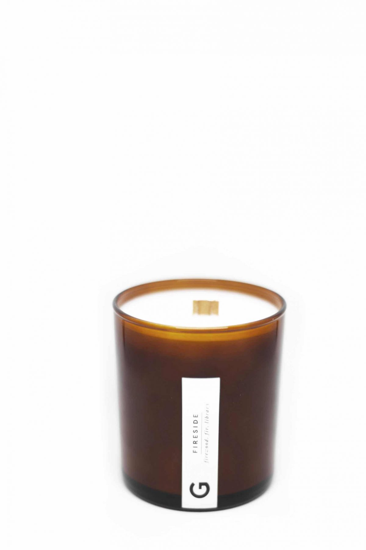 """Candle in amber colored glass. Wax is white with a natural wooden wick. A white horizontal label placed vertically displays a """"G"""" logo and reads """"FIRESIDE   firewood, fir, library"""""""
