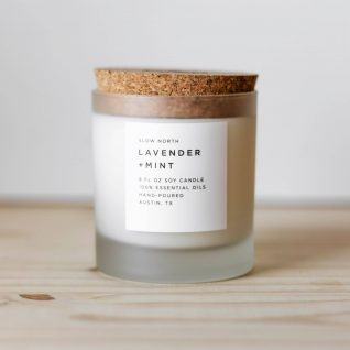 Frosted white candle on tan wood and white background