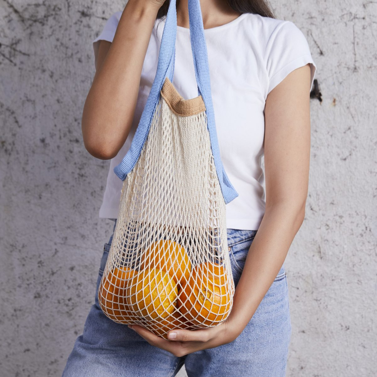 Woman holding a net bag with blue and nude colored straps filled with oranges