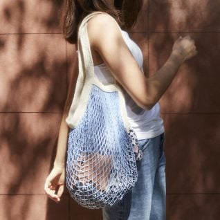woman walking outside carrying a blue colored net bag