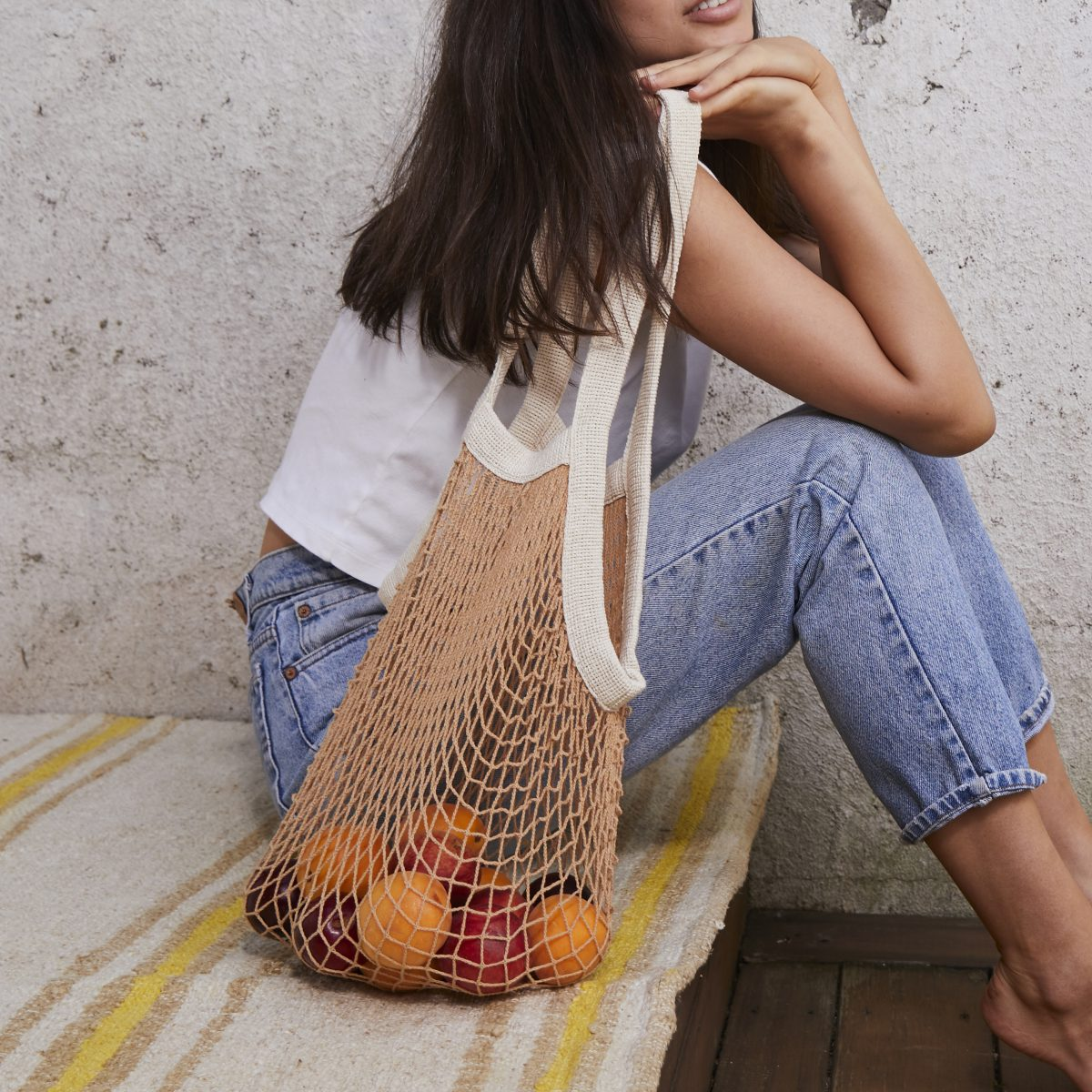 woman sitting outside holding a nude colored net bag filled with fruit